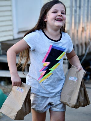 """MeiMei Bogart (7) carries her """"sparkles"""" Halloween treat bags to a home with children that requested the gift bags on Monday evening. MeiMei has handed out more than 800 bags to kids in eight different states, including Tennessee, Indiana and Illinois in less than seven months."""