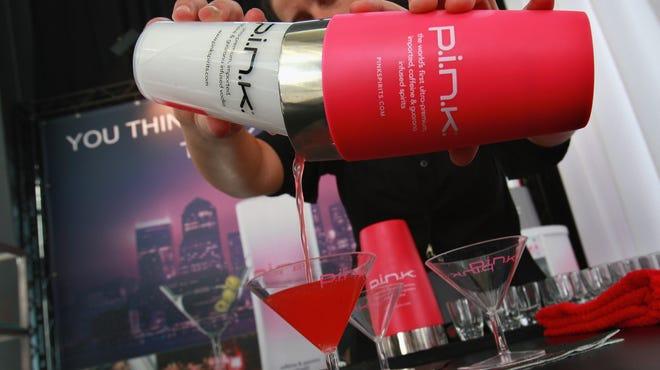 A host prepares a vodka cranberry cocktail.