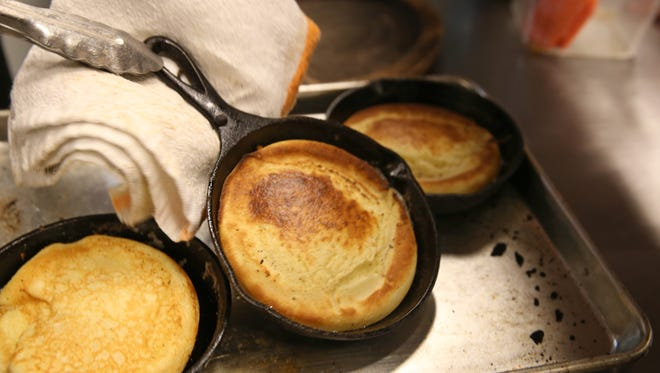 Cook Eric Jongsma carefully picks up hot cast iron skillets straight from the over as he flips each of three buttermilk pancakes during brunch at McCann's Local Meats on S. Clinton Avenue in Rochester Saturday, Feb. 25, 2017.