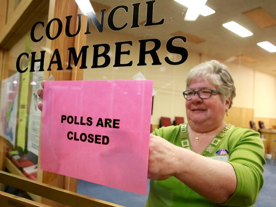 Election judge LaRae Atkinson tapes up a notice on Tuesday at Farmington City Hall.