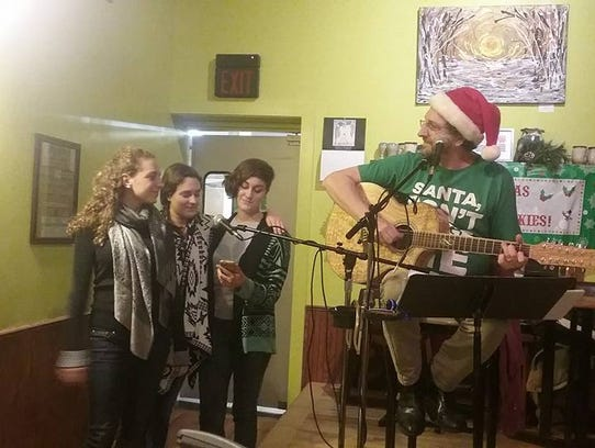Dave Cofell performs with his daughters, shown left