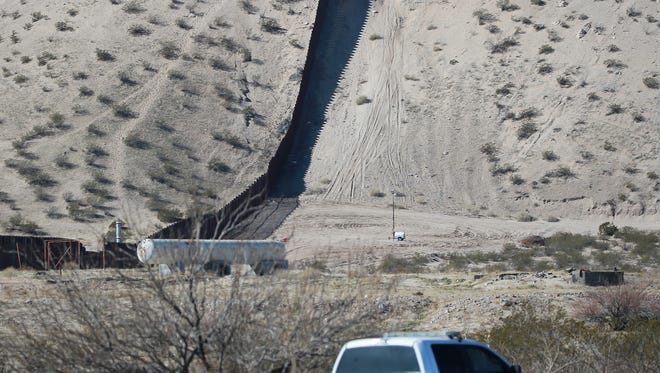 Border Patrol vehicles, top and bottom of photo, patrol the Sunland Park, N.M.-Anapra, Mexico, border.