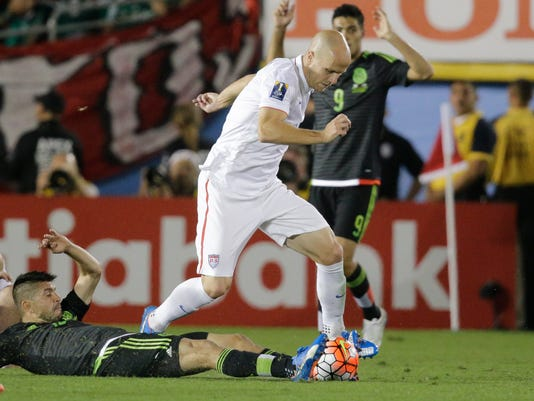 Mexico's Oribe Peralta, on the ground, attempts to take the ball from United States' Michael Bradley during the CONCACAF Cup soccer match at the Rose Bowl Stadium, in Pasadena , Calif. Saturday, Oct. 10, 2015, (AP Photo/Jae C. Hong)