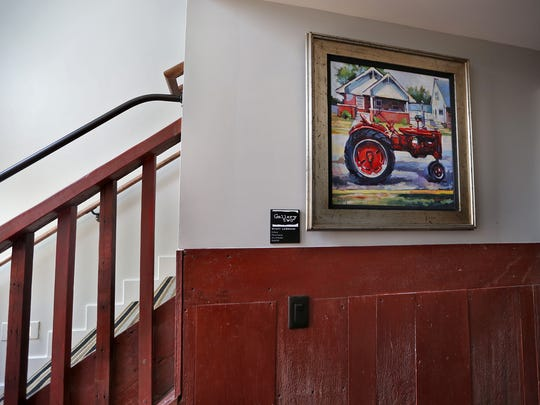 """Artwork from Fine Estate Art, like Wyatt LeGrand's """"En Route,"""" seen here in the Hotel Broad Ripple, Wednesday, May 21, 2014, will be on display, as the hotel acts as a gallery, also. This area is the connector between two parts of the hotel.  The walls are from a barn in Spiceland, IN."""