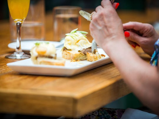 TRATA's Eggs Benedict consists of twin poached eggs with crisp pork belly, lemon sriracha hollandaise on toasted biscuits.