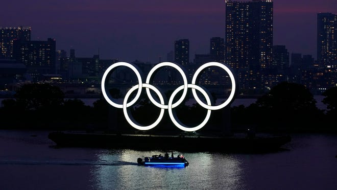 Tthe Olympic rings float in the water at sunset in the Odaiba section in Tokyo.