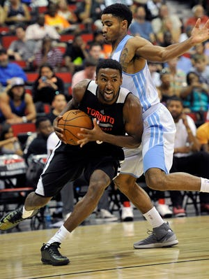 Toronto Raptor's Malcolm Lee, left, drives the ball against Denver Nuggets' Gary Harris during an NBA summer league basketball game.