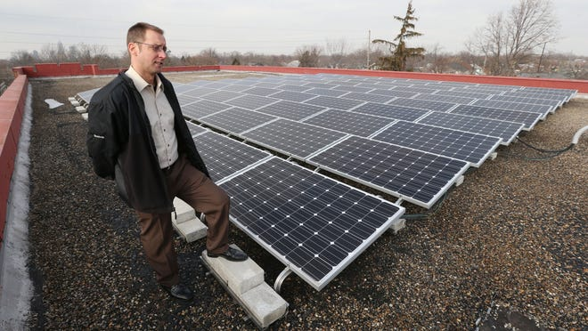 Joe Bowling, supervisor for the Englewood Solar Project, looks over solar panels Jan. 23, 2015, on the roof of the Englewood Christian Church, 57 N. Rural St., Indianapolis.