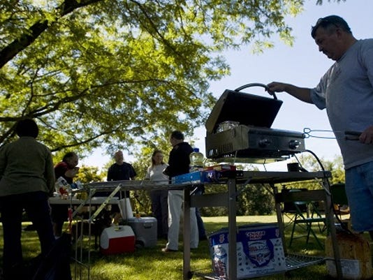 File photo; Bruce Hollinger, right, grills up food on a Saturday afternoon in September 2012.