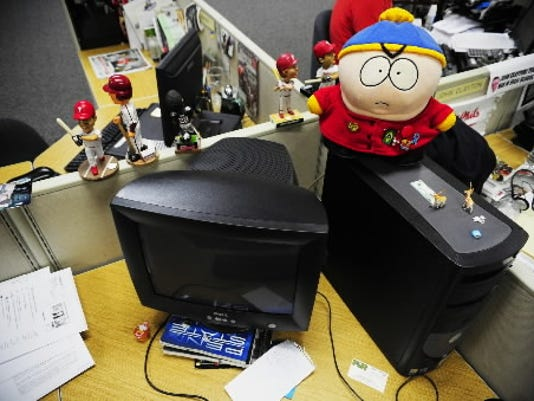 """A plush version of the """"South Park"""" character Cartman relaxes on the desk of award-winning sports reporter Frank Bodani. Daily Record/Sunday News -- Chris Dunn"""