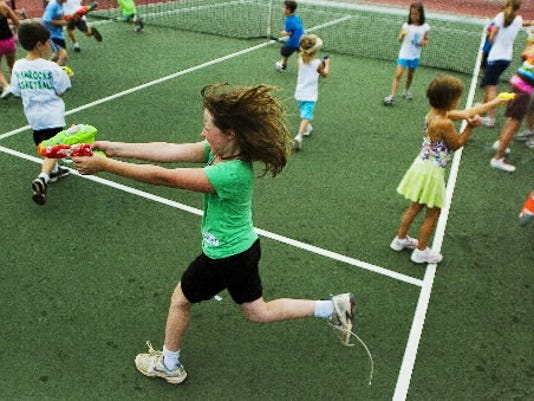 Emily Cougle, then 12, chases other kids through the South Western High School tennis courts with squirt guns in June 2011, during  Tennis for Kids camp. (Evening Sun -- Shane Dunlap)