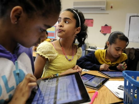 Last year, fifth-graders, from left, Sanai Brown, 10, Alexandria Baladejo, 11, and Lesly Fuentes Meza, 10, use iPads to connect to their social studies textbook at New Hope Academy Charter School. iPads were purchased through School Improvement Grant funding. (File photo)