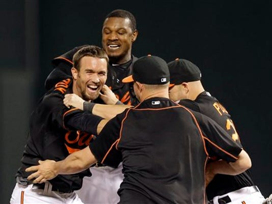 Baltimore's J.J. Hardy, left, celebrates with teammates after driving in the winning run in the ninth inning against the Tampa Bay Rays on Friday. Baltimore won 2-1.