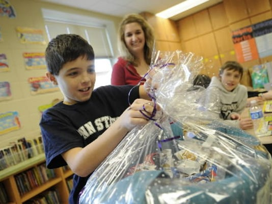 Zach Wherley, 11, opens a birthday basket full of low-fat treats at Manheim Elementary School. South Western School District sells Mini Mustang Birthday Baskets as a way to bring healthier foods into classroom celebrations.