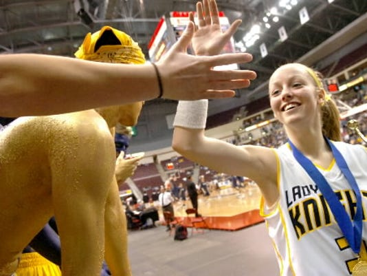 Eastern York girls' basketball player Brie Dohm, right, gets high-fives from fans as she carries the District 3 Class AAA championship trophy from the Giant Center floor on March 4, 2007, in Hershey.