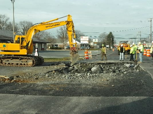 A crew of PennDOT workers watches as a worker uses an excavator to repair a sinkhole on Route 422 in front of the Palmyra Bowling Center and Sinkhole Saloon on Wednesday morning. The persistent subsidence reopened on Tuesday night, forcing a temporary closure of the road.