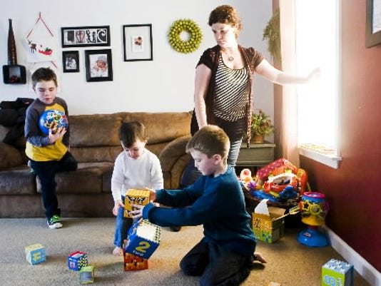 Jackson Salemme, 8, left, plays with a ball while his two brothers, Parker, 8, and Cooper, 3, play in the living room with their mother, Cara Salemme.
