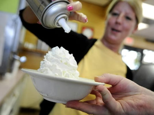 Jolene Krout tops a blondie sundae with whipped cream at Mack s Ice Cream in York Township.