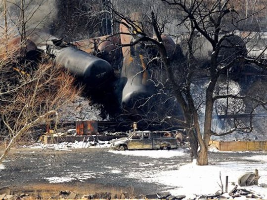 Train cars remain on the scene following a train derailment near Mount Carbon, W.Va., Tuesday, Feb. 17, 2015. A CSX train carrying more than 100 tankers of crude oil derailed Monday in a snowstorm, sending a fireball into the sky and threatening the water supply of nearby residents, authorities and residents said Tuesday. (AP Photo/The Register-Herald, Chris Jackson)