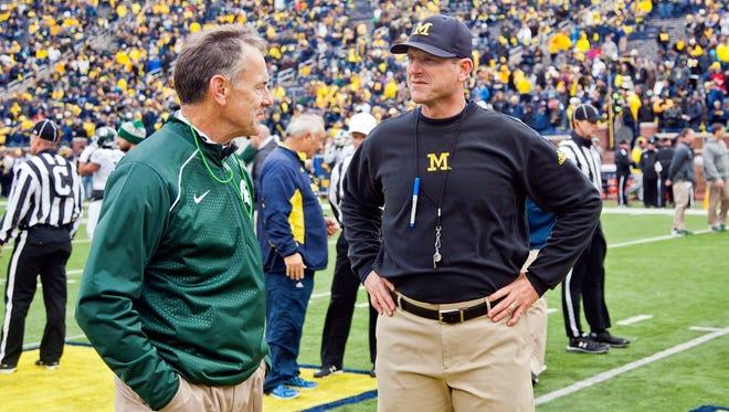 Michigan State head coach Mark Dantonio shakes hands with Michigan head coach Jim Harbaugh on the Michigan Stadium field before an NCAA college football game in Ann Arbor, Mich., Saturday, Oct. 17, 2015.
