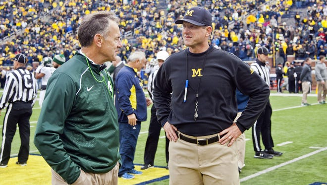 Michigan State coach Mark Dantonio, left, greets Michigan coach Jim Harbaugh before the Spartans' improbable 27-23 victory in 2015.