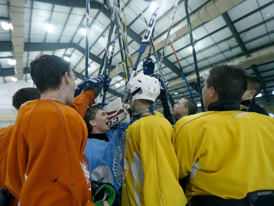 Wearing blue, Jeremy Audin joins the huddle at the