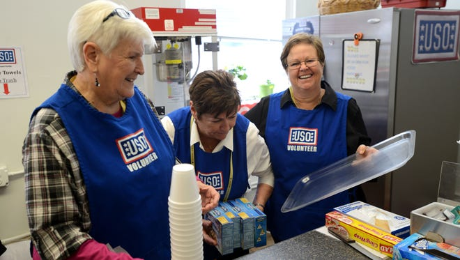 From left, USO of Northwest Florida volunteers Julie Collier, C.J. MacLean and Megan Marie McIver help put on the annual Thanksgiving meal and festivities in 2014 aboard Pensacola Naval Air Station.