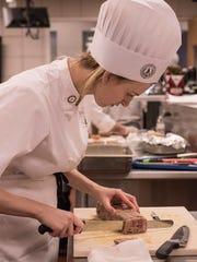 Kelsey Bylski slices her pork terrine.