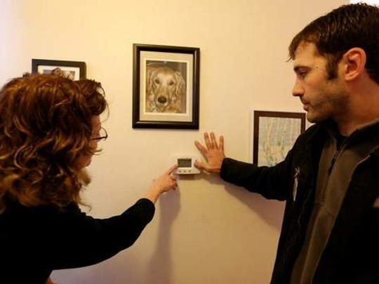 Cory Amos shows Jackie Wellman how to use the new programmable thermostat he installed. The two discussed what temperatures are comfortable for the family when they're at home and whether they can turn the heat down when they're sleeping or away.
