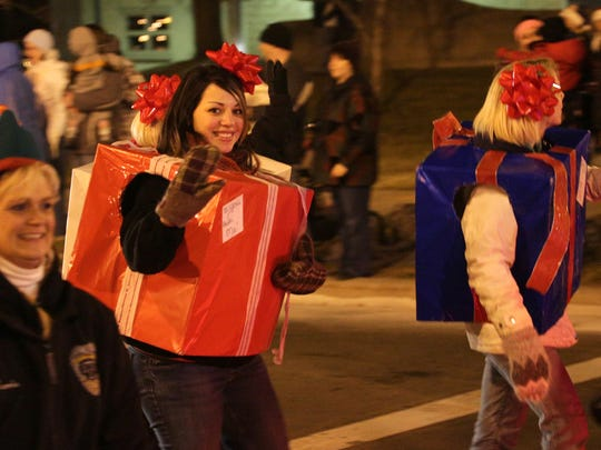 A young woman waves to the crowd during the Wausau Christmas Parade in 2012.