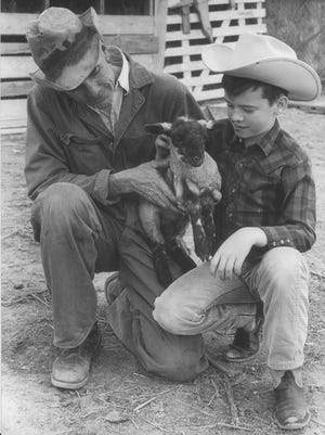 XB Cox Jr. and son XB Cox III inspect a newborn lamb in 1966.
