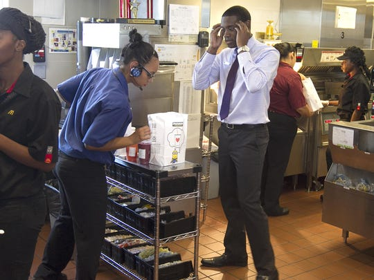 McDonald's manager Steven Chappell's tells his crew members to pick up the pace during a lunch-hour rush at the drive-thru Tuesday at the McDonald's at the Colonial Boulevard-State Road 82 intersection.