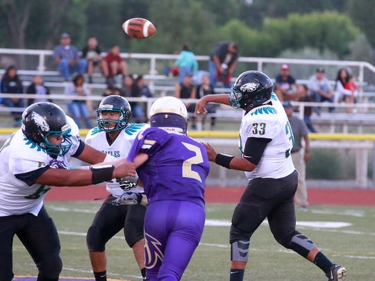 Navajo Prep senior Justin Cleveland throws a pass during a game against Kirtland Central  on Friday at Bronco Stadium.