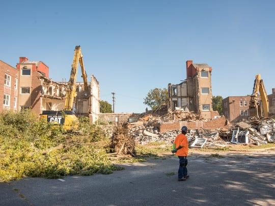 A worker watches the buildings being torn down. Demolition
