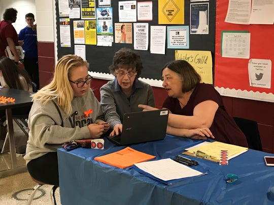 De Pere High School senior Emily Skinner works with Colleen Neuman, left, and Sandy Lubow of the Coalition of Voting Organizations of Brown County (COVO) to register to vote Friday afternoon.