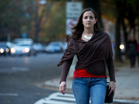 In this Nov. 11, 2014 photo, Laura Dunn, executive director of the sexual assault survivors' organization SurvJustice, crosses the street in her neighborhood in Washington. Dunn, a victim of sexual assault, believes an affirmative consent standard could have helped her 2004 case during campus judicial proceedings, which failed to find wrongdoing, even after appeals. (AP Photo/Manuel Balce Ceneta)