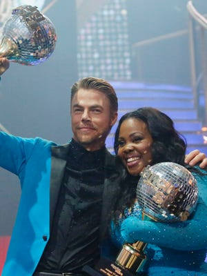 Season 17 champs Derek Hough and Amber Riley celebrate with their mirror ball trophies on 'Dancing With the Stars.'