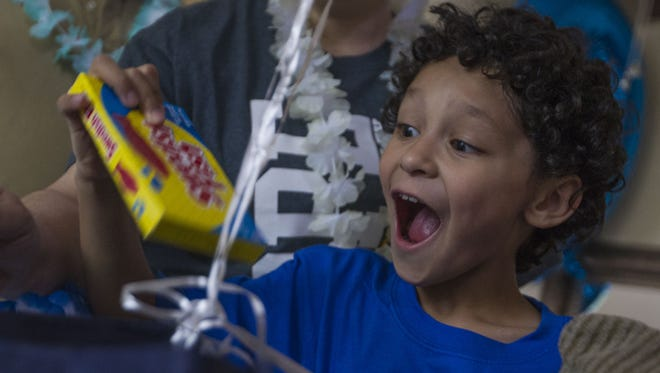 Bentley Brazlovitz reacts to gifts he opens for their upcoming trip to Hawaii. Bentley is nearing one year in remission after battling embryonal rhabdomyosarcoma, a soft tissue cancer. Johanna Huckeba/azcentral
