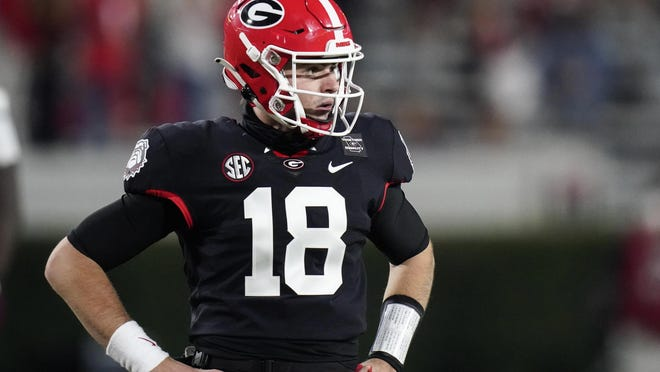 Georgia quarterback JT Daniels (18) looks for a play call from the sideline during the first half of an NCAA college football game against Mississippi State, Saturday, Nov. 21, 2020, in Athens, Ga.