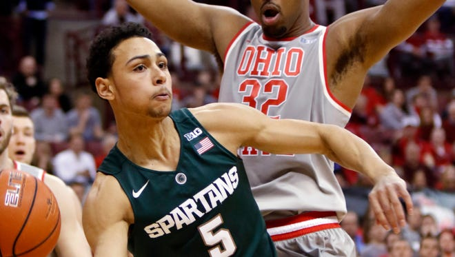 Michigan State's Bryn Forbes (5) passes the ball as Ohio State's Trevor Thompson (32) defends during the first half Tuesday in Columbus, Ohio.