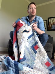 Barrett Baber holds the burned quilt recovered from