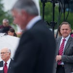 Alabama Supreme Court Justice Tom Parker, left, and Chief Justice Roy Moore, right, look on as Rev. Franklin Graham speaks in front of the state capitol building in Montgomery, Ala. on Thursday April 14, 2016 as part of his Decision America Tour.