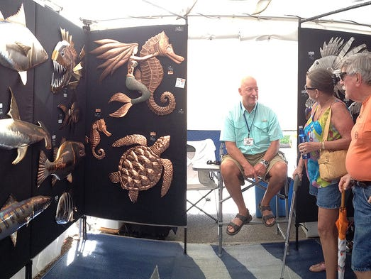 In this panoramic photo Lucy and Jim Oldham talk with artist Ted Elder, seated, while surrounded by a whole ecosystem of his Hammerhead Marine Sculptures featuring  different types of sea life at his booth at the Pensacola Seafood Festival Friday afternoon.