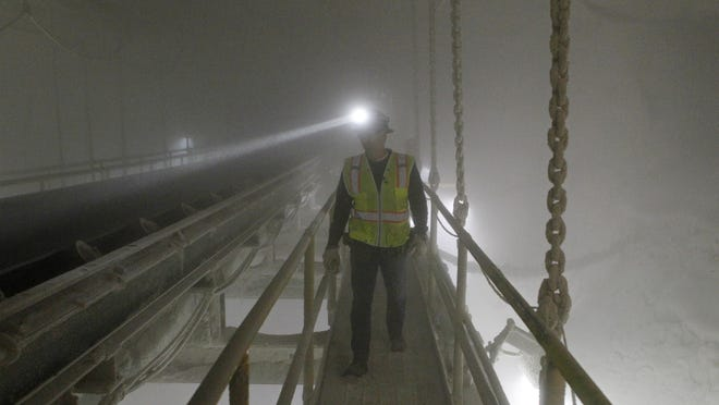 An American Rock Salt Co. mine production worker inspects the surge bin at the mine in Hampton Corners, N.Y.