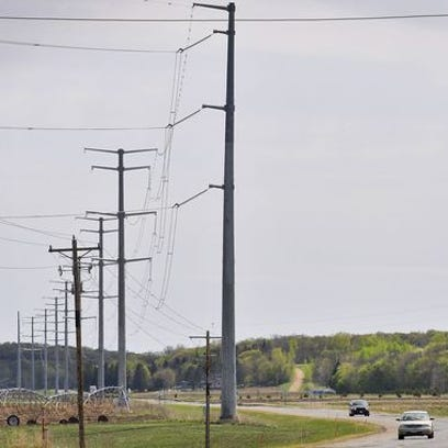 Electrical transmission towers from the completed CapX2020 powerline project loom over farmland as cars travel along Stearns County Road 2 in May between St. Joseph and Cold Spring. CapX is helping make Xcel Energy the top property taxpayer in Stearns County.