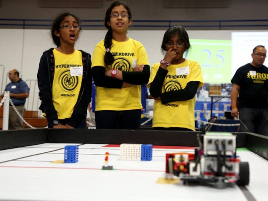 (L to R) Ananya Parimi, 11, Ankitha Challa, 10, and Shreya Pattisapu, 11, all from Aurora, Ill. watch and react as their programmable robot goes along collecting LEGO items during the World Robot Olympiad USA 2014 National Championship at the Don Ridler Field House on the campus of Lawrence Technological University in Southfield on Saturday, Sept. 27, 2014.
