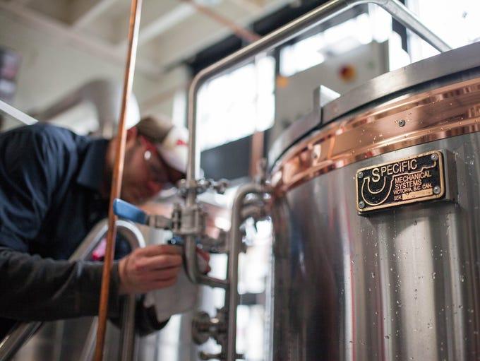 Head Brewer Jamie Feihel cleans the stills and prepares