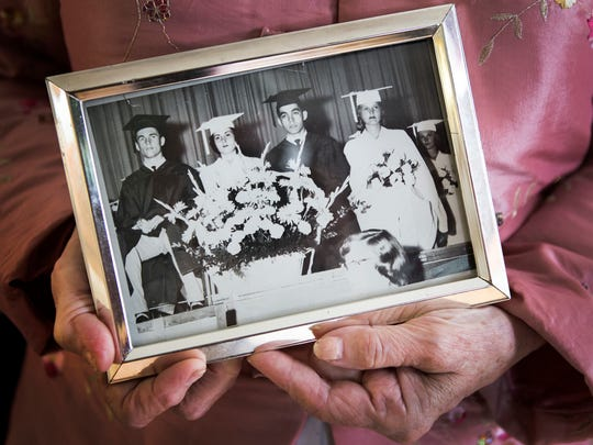 Joanna Caputo holds a photo of herself (second from left) from her high school graduation on Thursday afternoon.