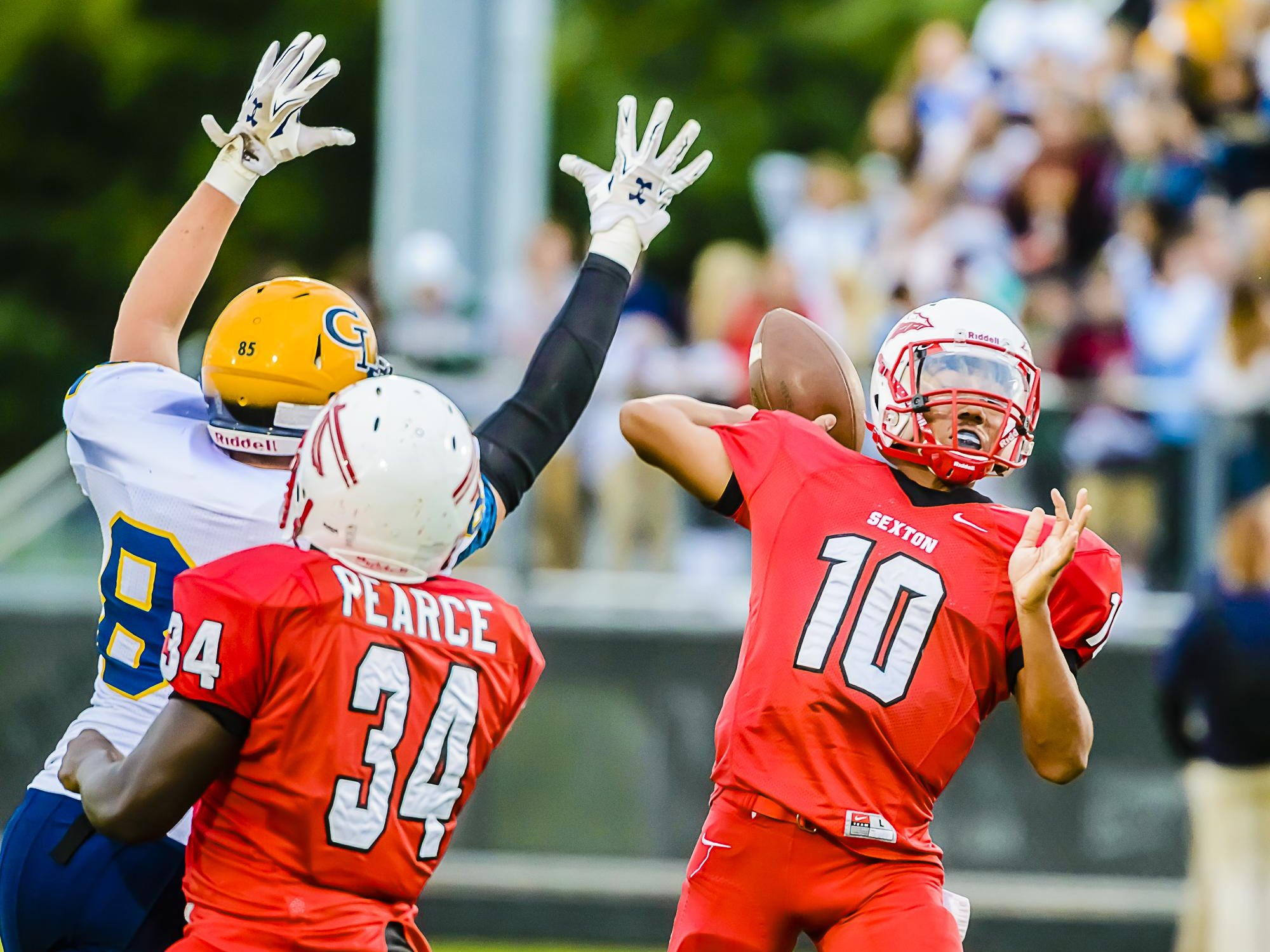 Sexton quarterback Mike Lynn III ,10, passes to teammate Devin Taylor for a touchdown while under pressure from a Grand Ledge defender in the 1st quarter of their game Friday September 11, 2015 at Sexton High in Lansing. KEVIN W. FOWLER PHOTO