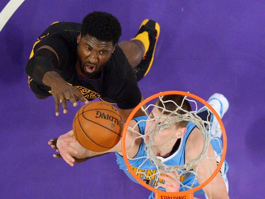 Los Angeles Lakers center Roy Hibbert, left, shoots as Denver Nuggets center Nikola Jokic defends during the first half of an NBA basketball game, Friday, March 25, 2016, in Los Angeles. AP Photo/Mark J. Terrill)